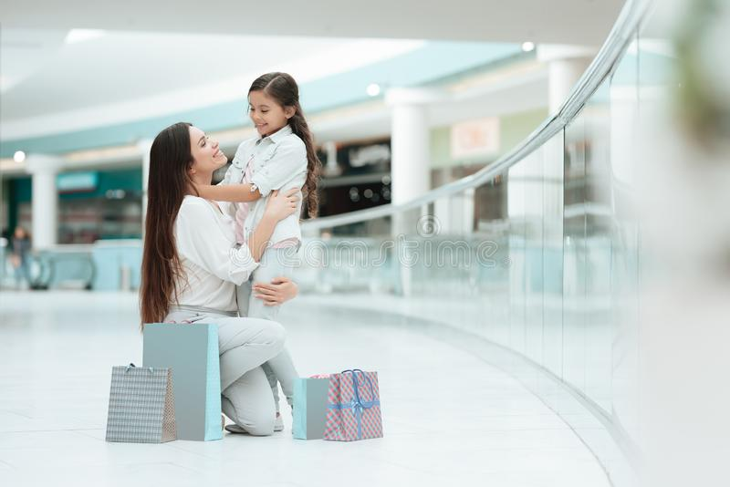 Daughter is sitting on mother`s lap in shopping mall. Mom and girl are smiling. stock photo