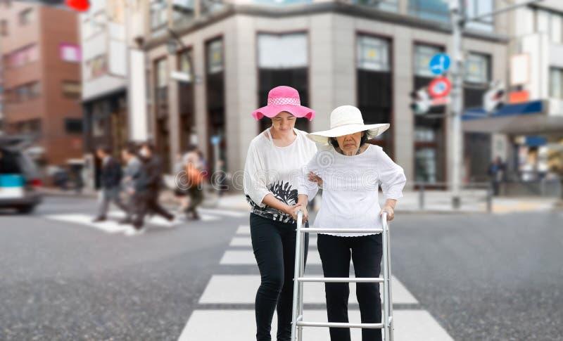 Daughter take care elderly walking across the street royalty free stock photo