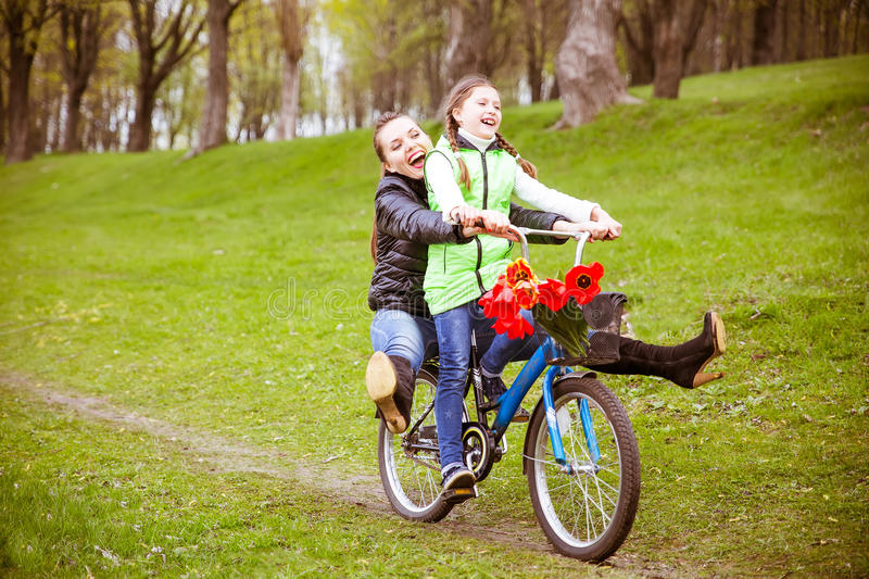 The daughter takes her mother on a Bicycle on the lake in the Park . They're having fun. royalty free stock photography