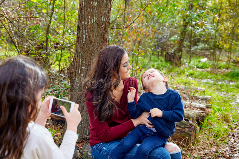 Daughter taking mobile photo mother and son. Daughter taking mobile photo of mother and son brother in the park having fun royalty free stock photos