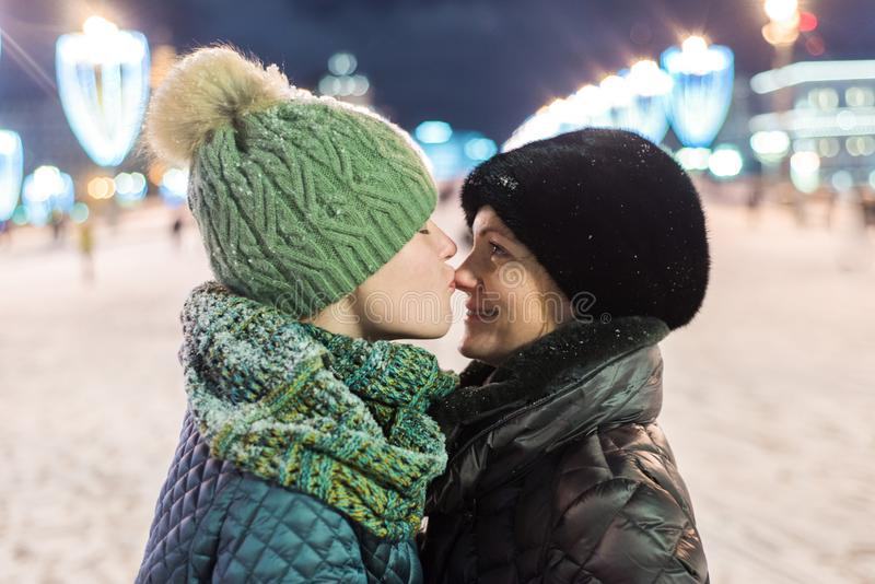 Daughter teenager gently kisses his mother in the nose while standing on a nightly brightly lit street in winter. Mother and daughter in winter clothes. It& royalty free stock images
