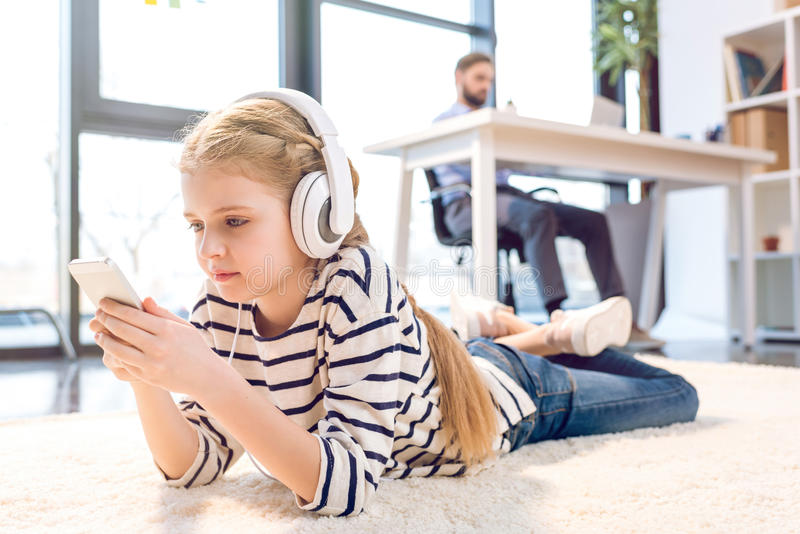 Daughter using smartphone and headphones, businessman working behind in office stock photos