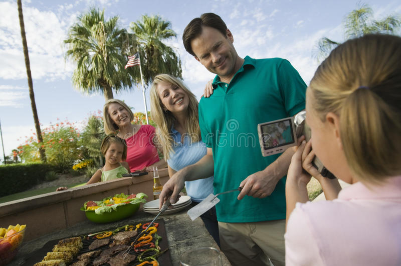 Daughter (7-9) video taping parents grandmother sister (7-9) at outdoor barbecue. royalty free stock photos