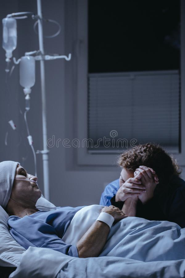 Daughter visiting sick mother with cancer dying in the hospital royalty free stock photography