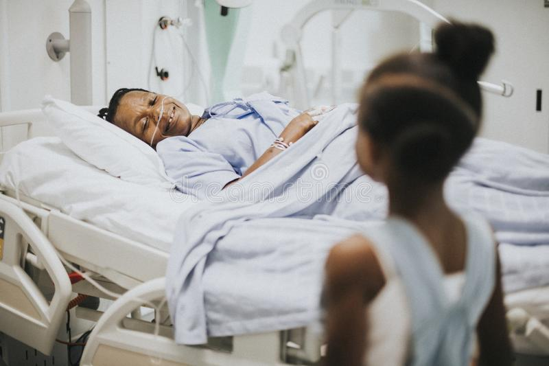 Daughter watching her grandmother sleep at the hospital stock photos