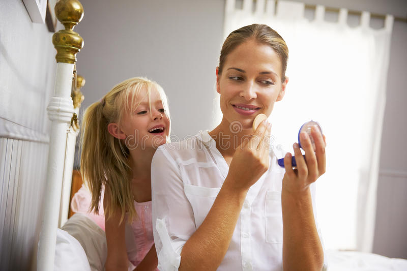 Daughter Watching Working Mother Put On Make Up royalty free stock photos