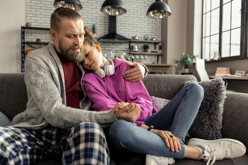Daughter wearing jeans and sneakers leaning on shoulder of father royalty free stock image