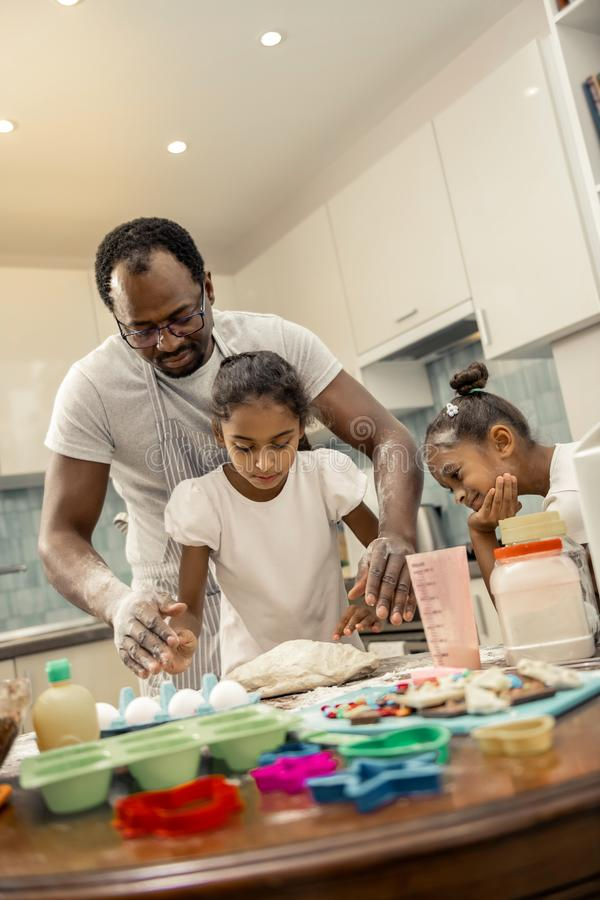 Daughters and father cooking cupcakes for breakfast in the morning. Cupcakes for breakfast. Daughters and father feeling good cooking cupcakes for breakfast in stock photography