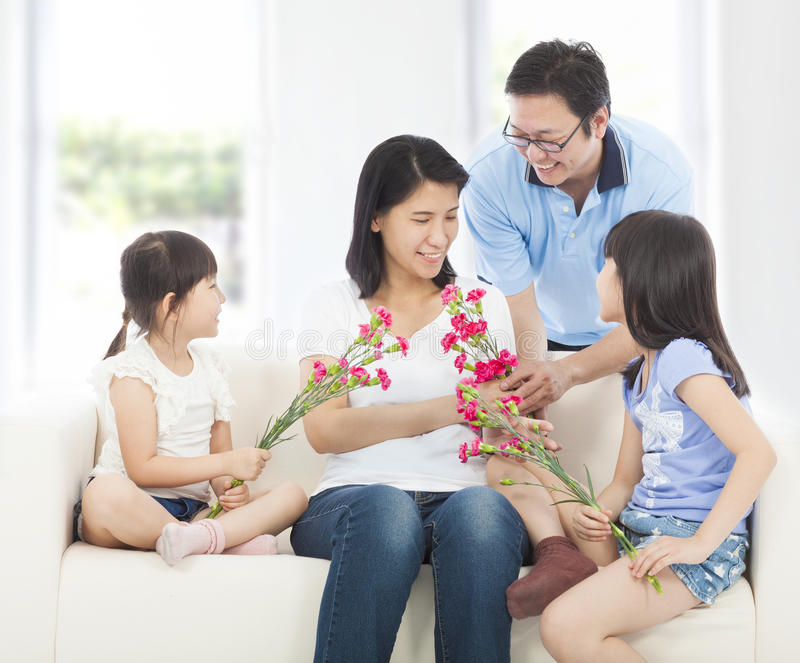 Daughters and father handing mother carnations stock images