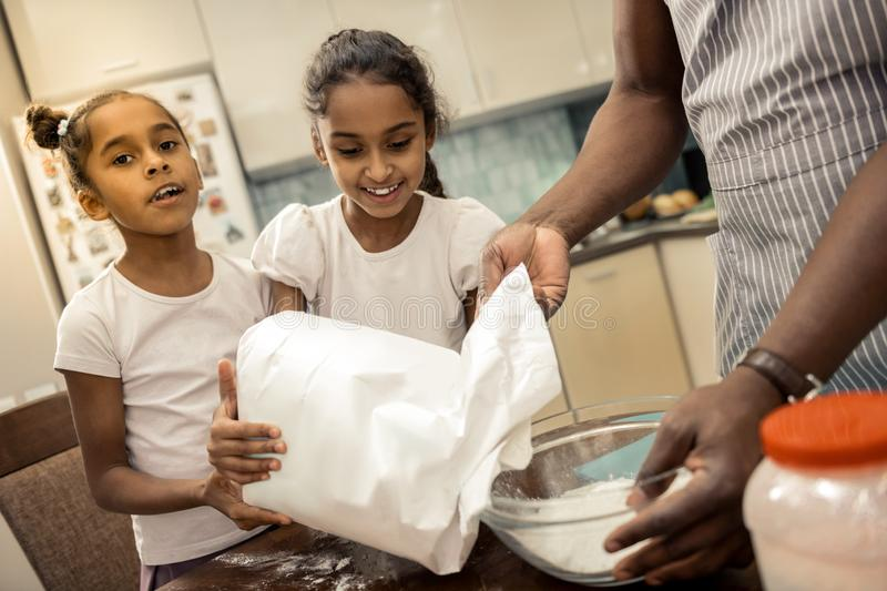 Daughters feeling cheerful and memorable while cooking with father. Cooking with father. Two daughters feeling cheerful and memorable while cooking with their royalty free stock images