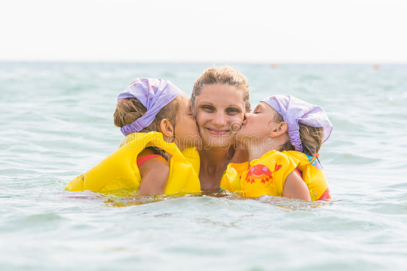 Daughters kiss mom swimming in sea stock photo