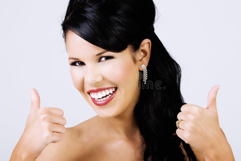 Daumen oben von der schönen lächelnden Frau stockfoto