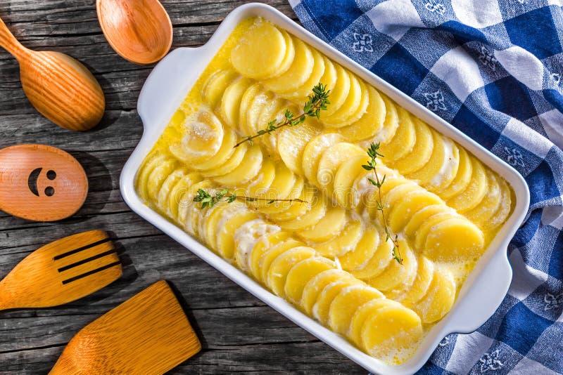 Dauphinois alla griglia, patate ha preparato per la torrefazione in una pentola immagini stock