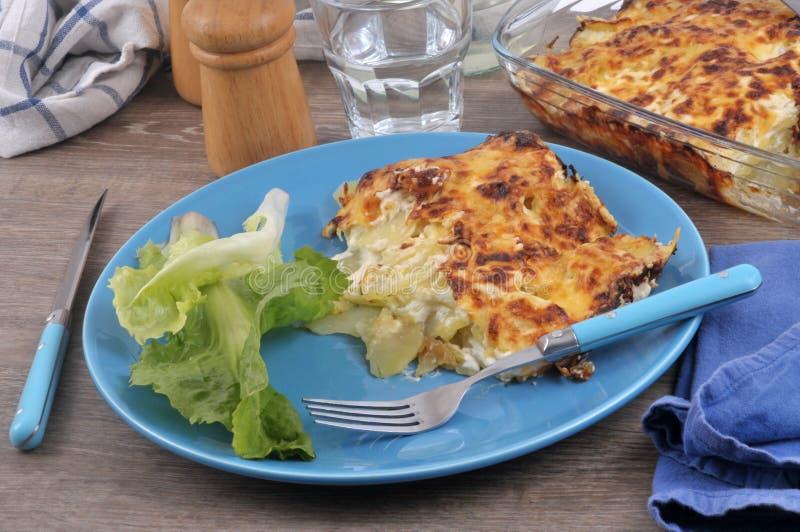 Dauphinois del gratin e foglie dell'insalata immagini stock