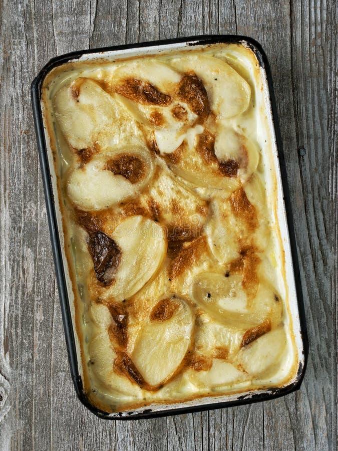 Dauphinois horneados a la crema y con pan rallado de oro rústicos del gratén de la patata fotos de archivo libres de regalías