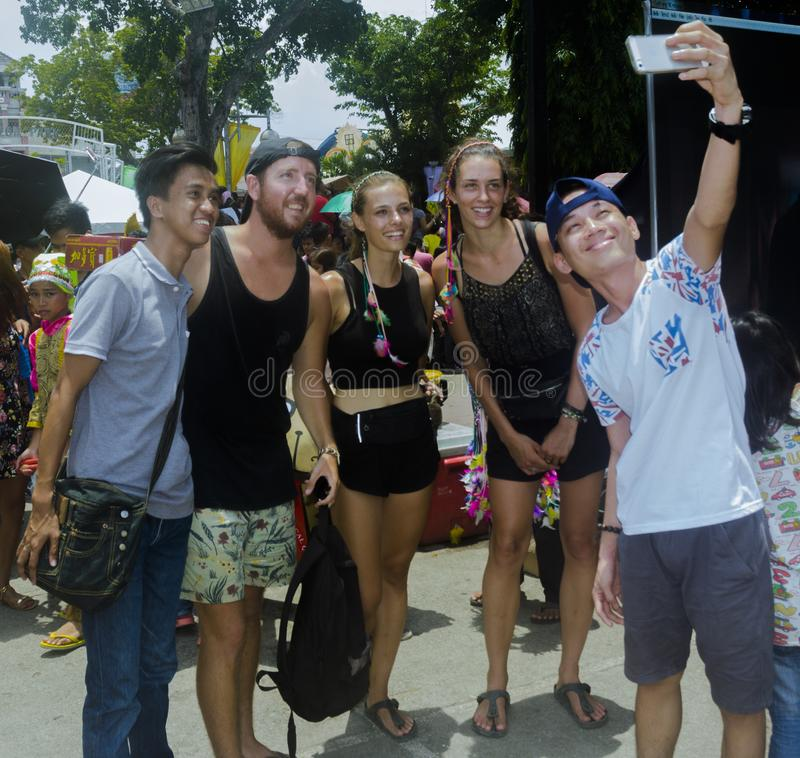 Locals selfie with tourists during 2018 Kadayawan Festival in Davao. Davao, Philippines - August 18, 2018: Locals having selfie with tourists during Kadayawan stock images
