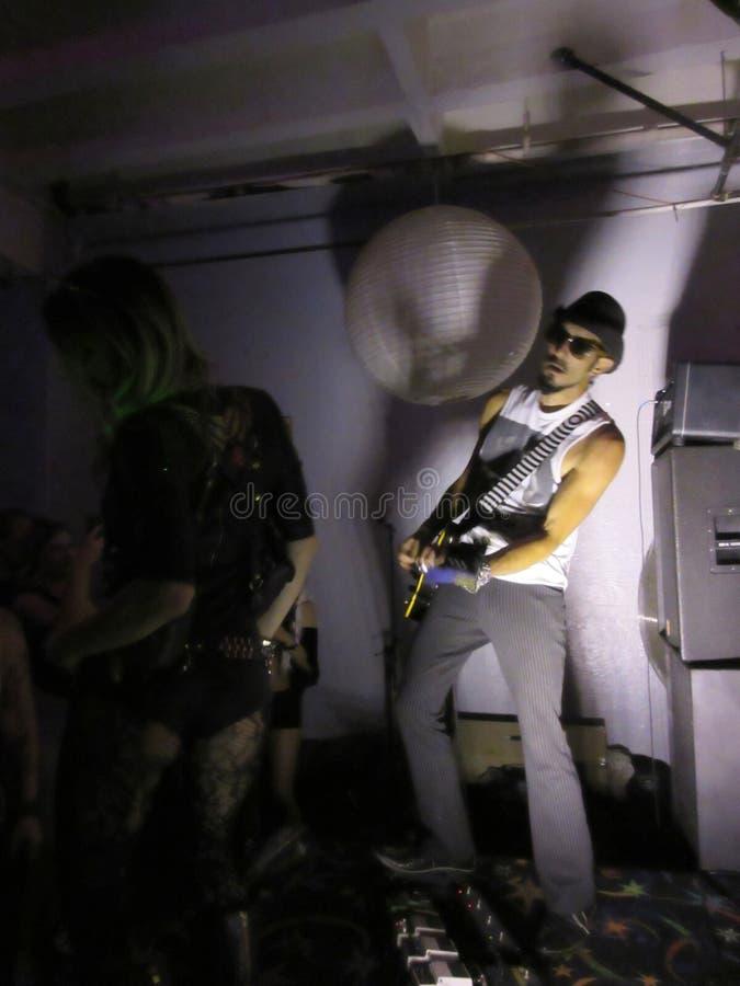 Dave Edery joga a guitarra na fase enquanto os povos party no subterrâneo fotos de stock royalty free