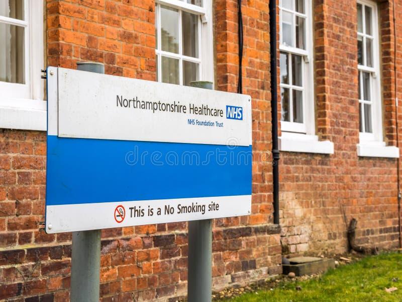 Daventry,英国2018年3月23日:北安普敦郡医疗保健NHS基础信任与警告此的路标禁烟 图库摄影
