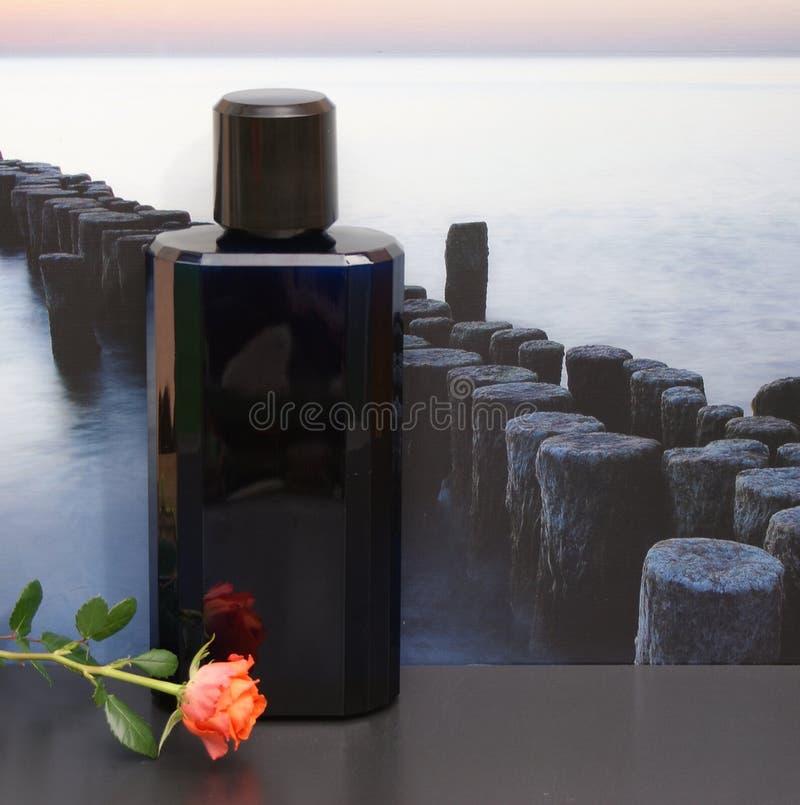 Davidoff dekorerade kallt vatten, Eau de Toilette, den stora doftflaskan framme av bilden av en vågbrytare i havet med en ros royaltyfria foton