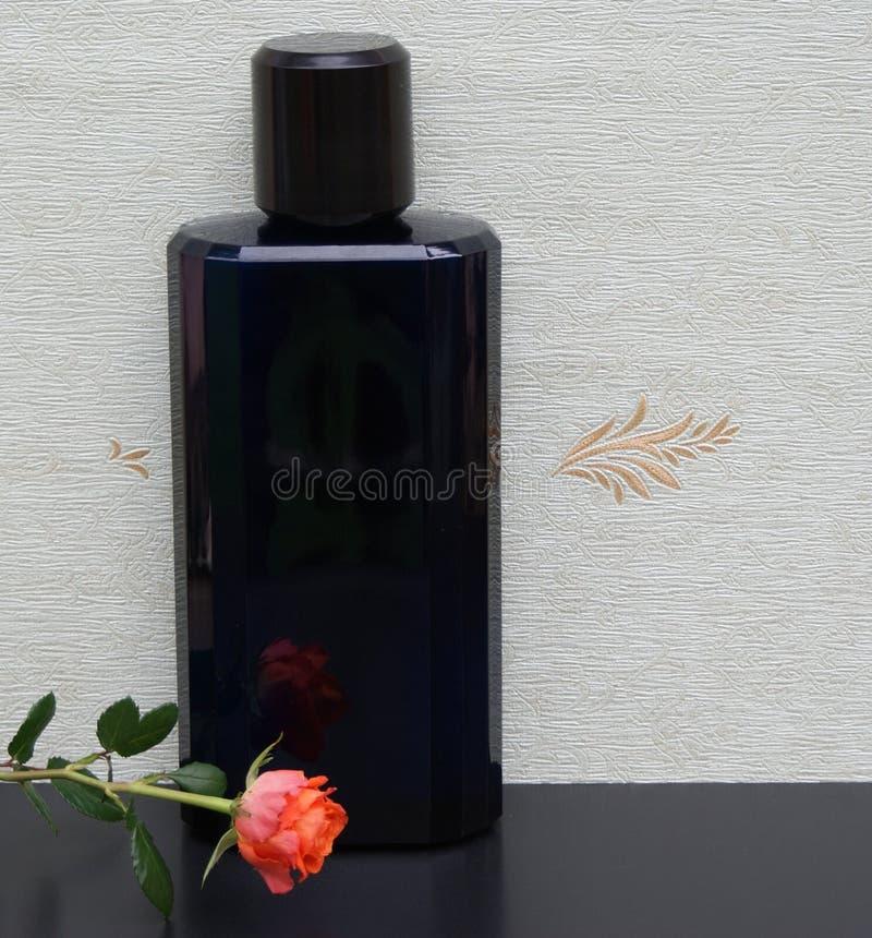 Davidoff dekorerade kallt vatten, Eau de Toilette, den stora doftflaskan framme av satängwallcoveringen Elysee med en ros arkivbild
