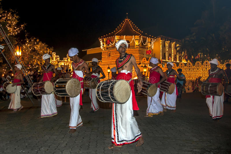 Davul Players perform in front of the Temple of the Sacred Tooth Relic in Kandy, Sri Lanka during the Esala Perahera. The playing of this drum is considered stock photo