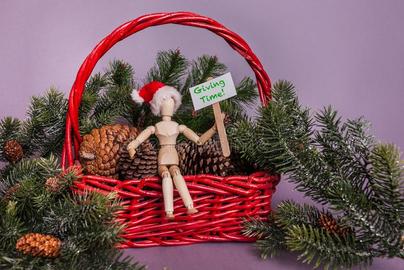 Dawać czas wiadomości trzymającej drewnianym spajającym manikin lali obsiadaniem w czerwony koszykowy pełnym pinecones i sosnowa  obraz royalty free