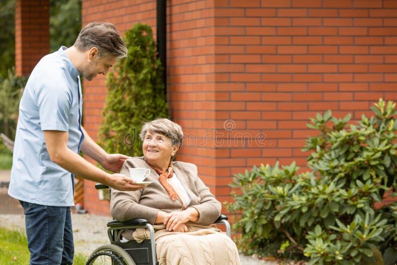 Dawać filiżance herbata uśmiechać się niepełnosprawnej starszej kobiety w wózku inwalidzkim fotografia stock