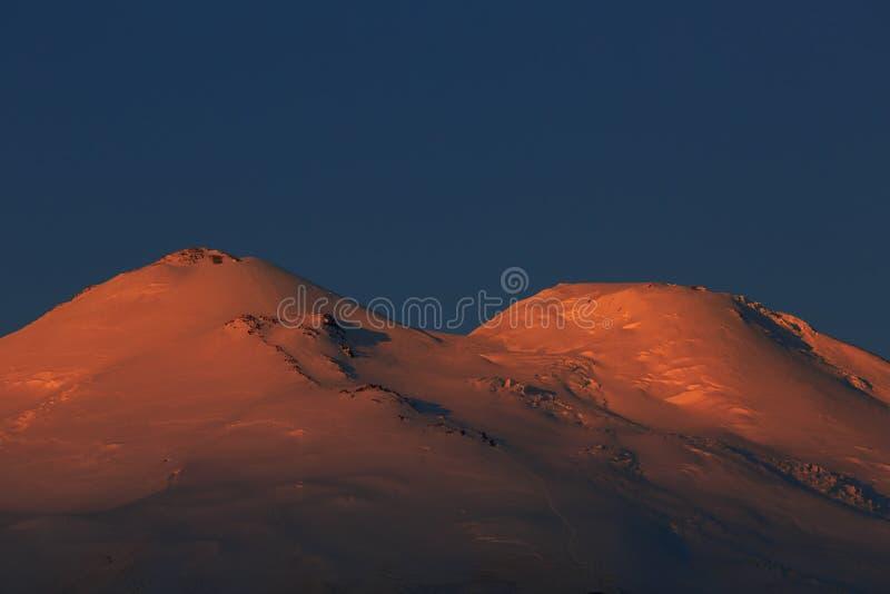 Dawn πέρα από τις χιονοσκεπείς αιχμές του υποστηρίγματος Elbrus στοκ εικόνα