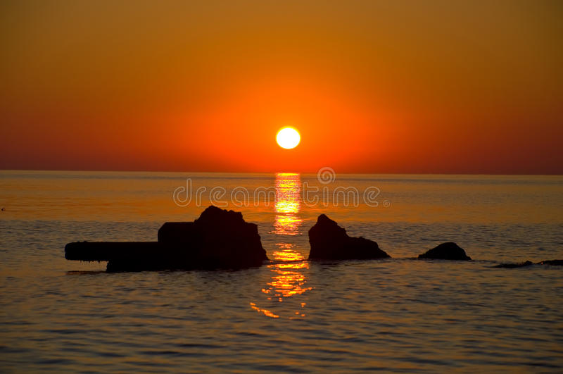 Dawn. Beautiful dawn with a gold reflexion on ripples of the sea and stones royalty free stock image