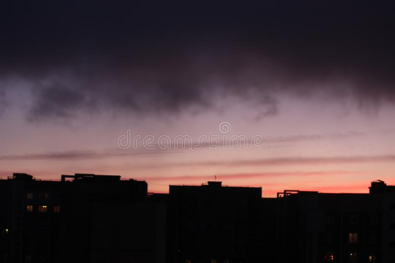 Dawn against the dark sky with clouds, colorful sky from the rising sun stock image