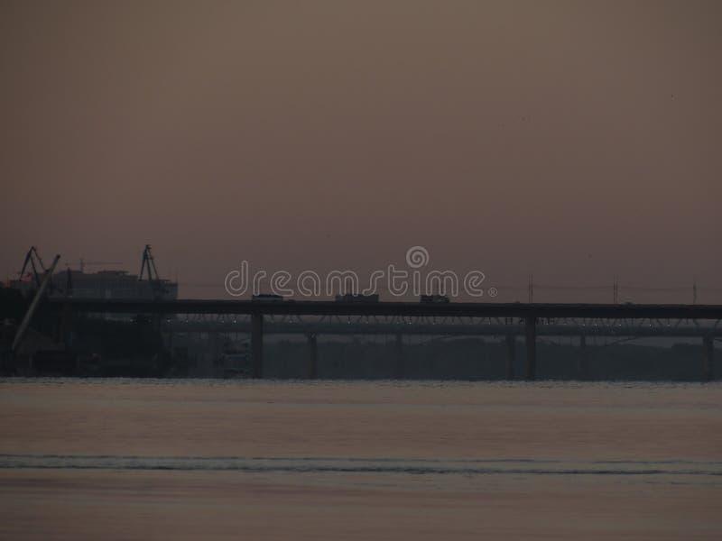 Dawn cityscape met een zwarte contour van de ochtendbrug tegen de hemel en de rivier stock afbeeldingen