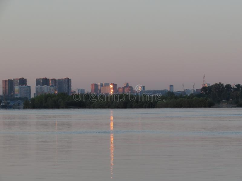 Dawn cityscape with reflection in the river water of bright orange flare in the window of the house. royalty free stock photos
