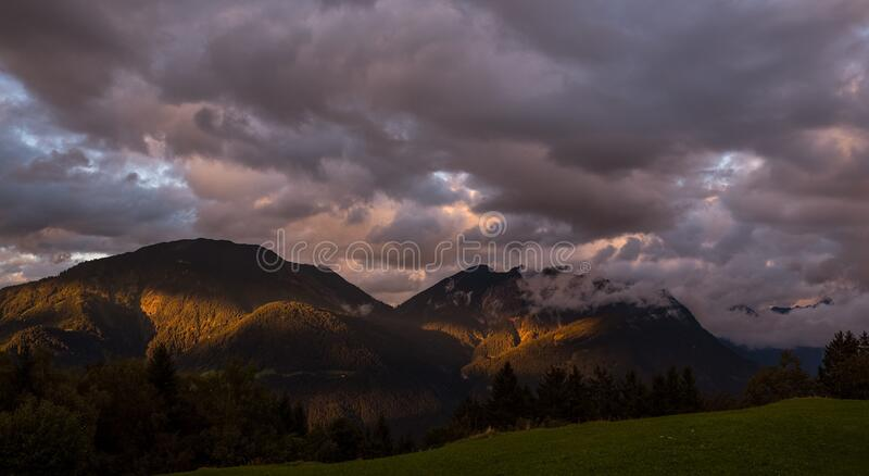 Dawn through clouds over mountain peaks royalty free stock photography