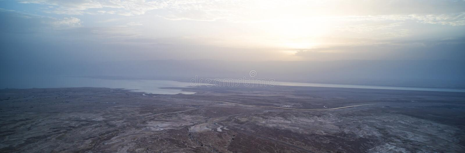 Dawn of the dead sea panorama. Beautiful sunset on the dead sea in front of the Judean desert. The sun Peeps out from behind the. Clouds. Beautiful Landscape of stock photo