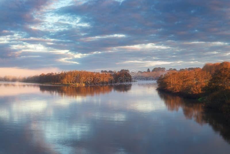 Dawn in een mist op de rivier De herfstochtend Een mist over water De zon in een mist Vroege ochtendzonsopgang gloed en het toene royalty-vrije stock fotografie