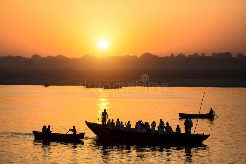 Dawn on the Ganges river, with the silhouettes of boats with pilgrims. Varanasi. India stock photography