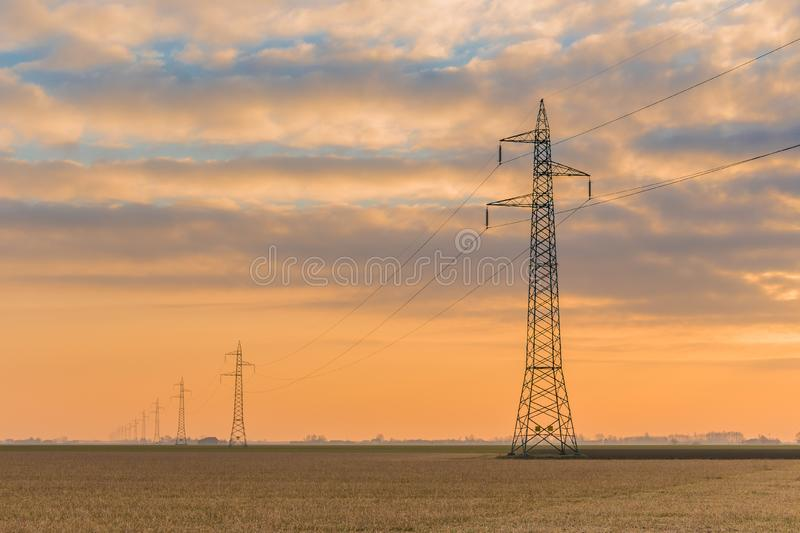 Dawn on high voltage pylons. In the Italian countryside stock photography