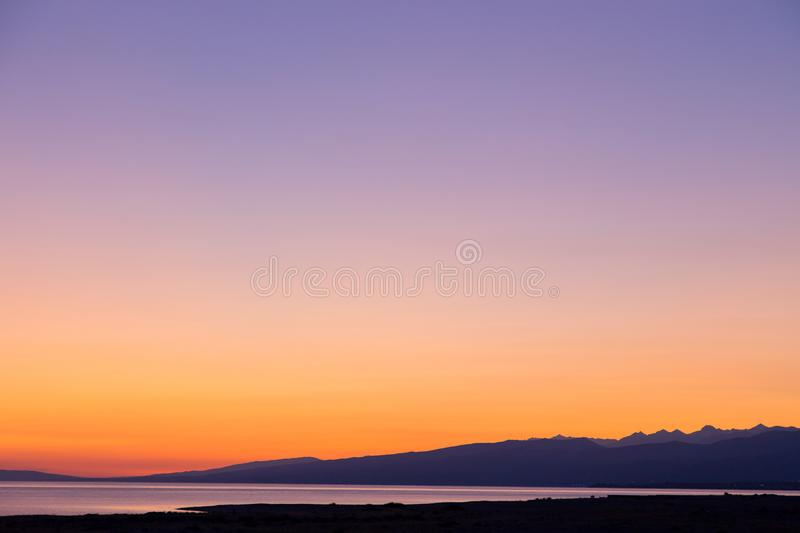 Dawn on a lake in the mountains. rays of the rising sun, orange color. Kyrgyzstan, Issyk-Kul Lake. Beautiful sunset on a lake in the mountains. Kyrgyzstan, Issyk stock images