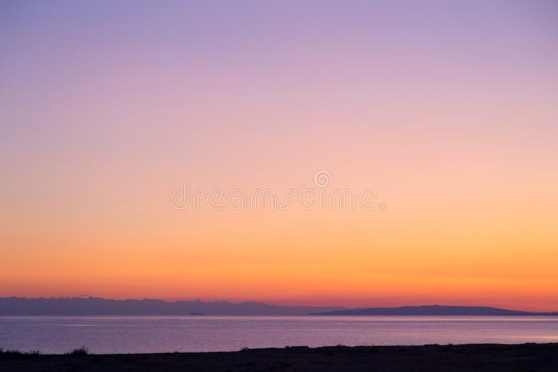 Dawn on a lake in the mountains. rays of the rising sun, orange color. Kyrgyzstan, Issyk-Kul Lake. Beautiful sunset on a lake in the mountains. Kyrgyzstan, Issyk stock photography