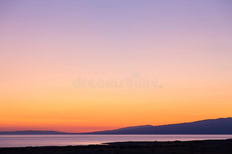 Dawn on a lake in the mountains. rays of the rising sun, orange color. Kyrgyzstan, Issyk-Kul Lake. Beautiful sunset on a lake in the mountains. Kyrgyzstan, Issyk royalty free stock photo