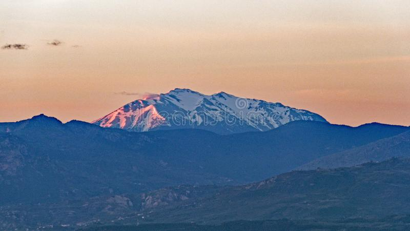 Dawn Light on Fresh Snow Capped Peloponnese Mountains, Greece. Early morning post dawn pink light on fresh spring snowfall on Peloponnese mountains, Greece stock photo