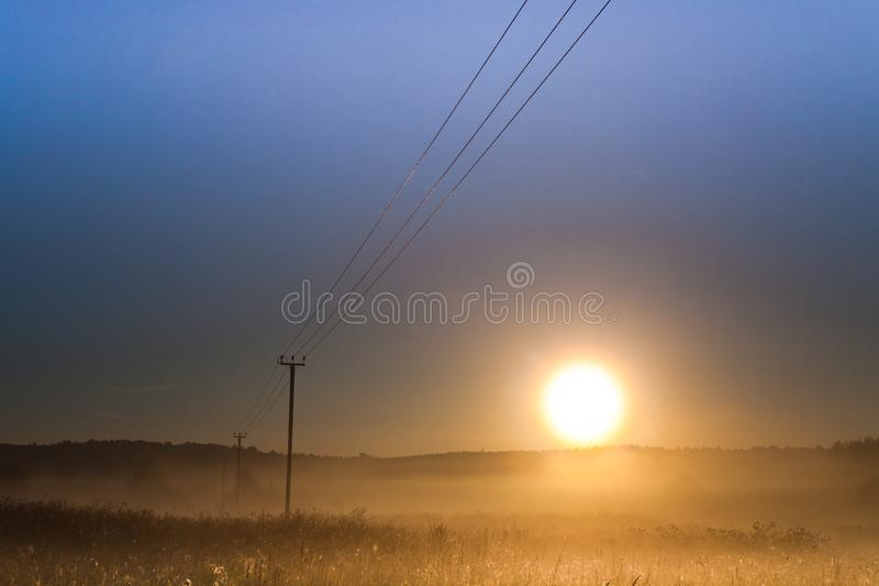 Dawn, the morning sun rises over the field and power transmission line, foggy dawn landscape, wires create lines stock photography