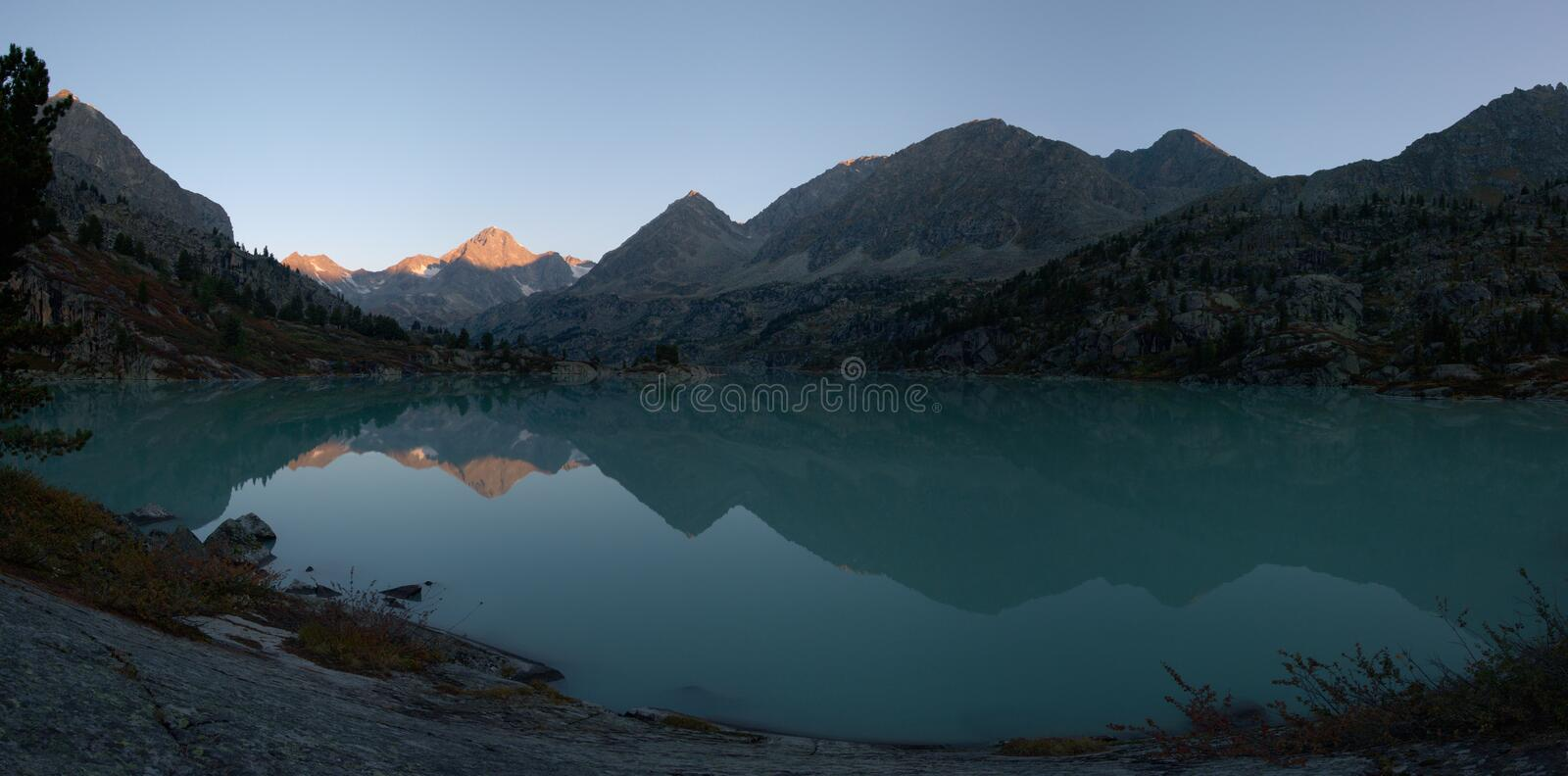 Dawn in mountains lake stock photography