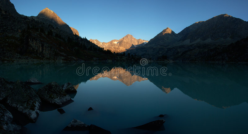 Dawn in mountains on lake stock images