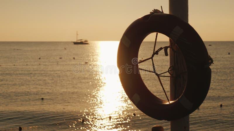 Dawn op het overzees, in de voorgrond hangt een het levensring, in de afstand is het schip zichtbaar Toneellandschap vroeg royalty-vrije stock foto's