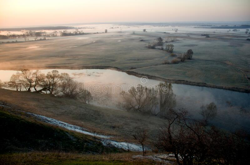 Dawn over a misty meadow and river on a spring morning. Easter morning, horizontal photo from a high slope royalty free stock image