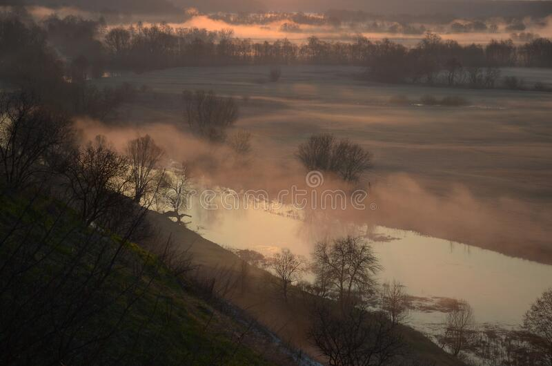 Dawn over a misty meadow and river on a spring morning. Easter morning, horizontal photo from a high slope royalty free stock photography