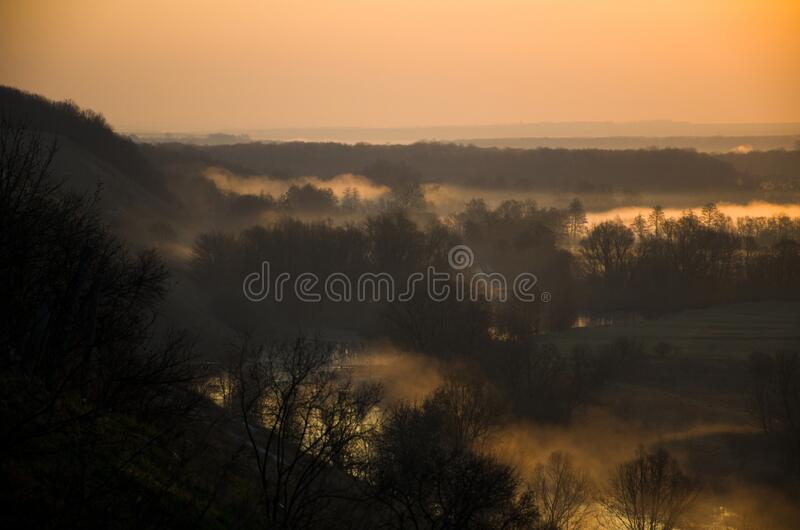 Dawn over a misty meadow and river on a spring morning. Easter morning, horizontal photo from a high slope royalty free stock images
