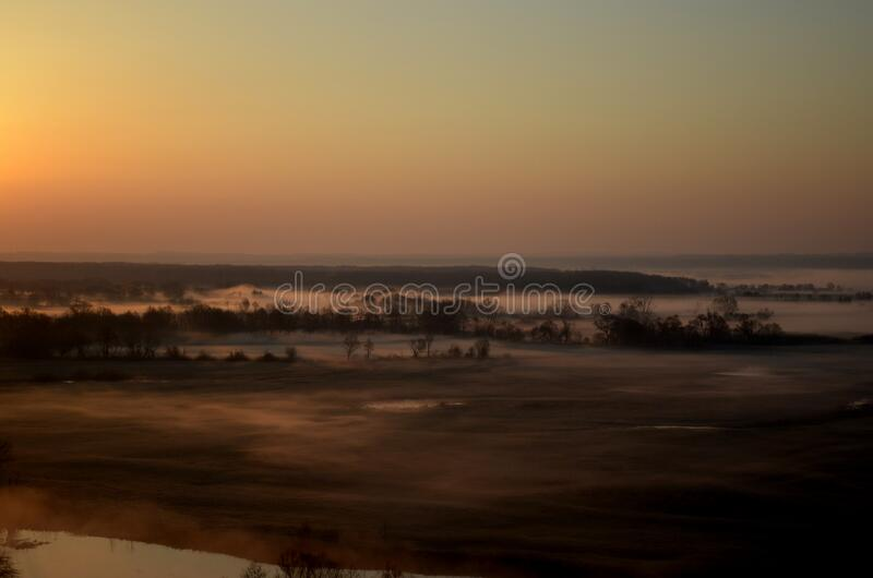 Dawn over a misty meadow on a spring morning. Easter morning, horizontal photo from a high slope stock images