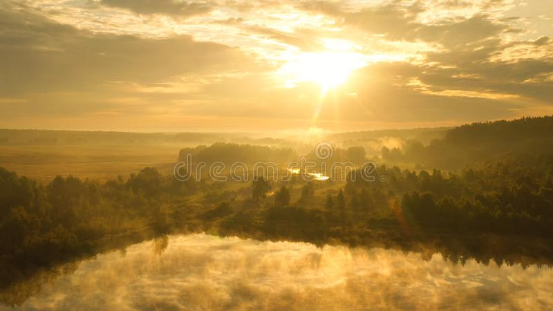 Dawn over the river, fog slowly rising from the water, its rays illuminate it stock images